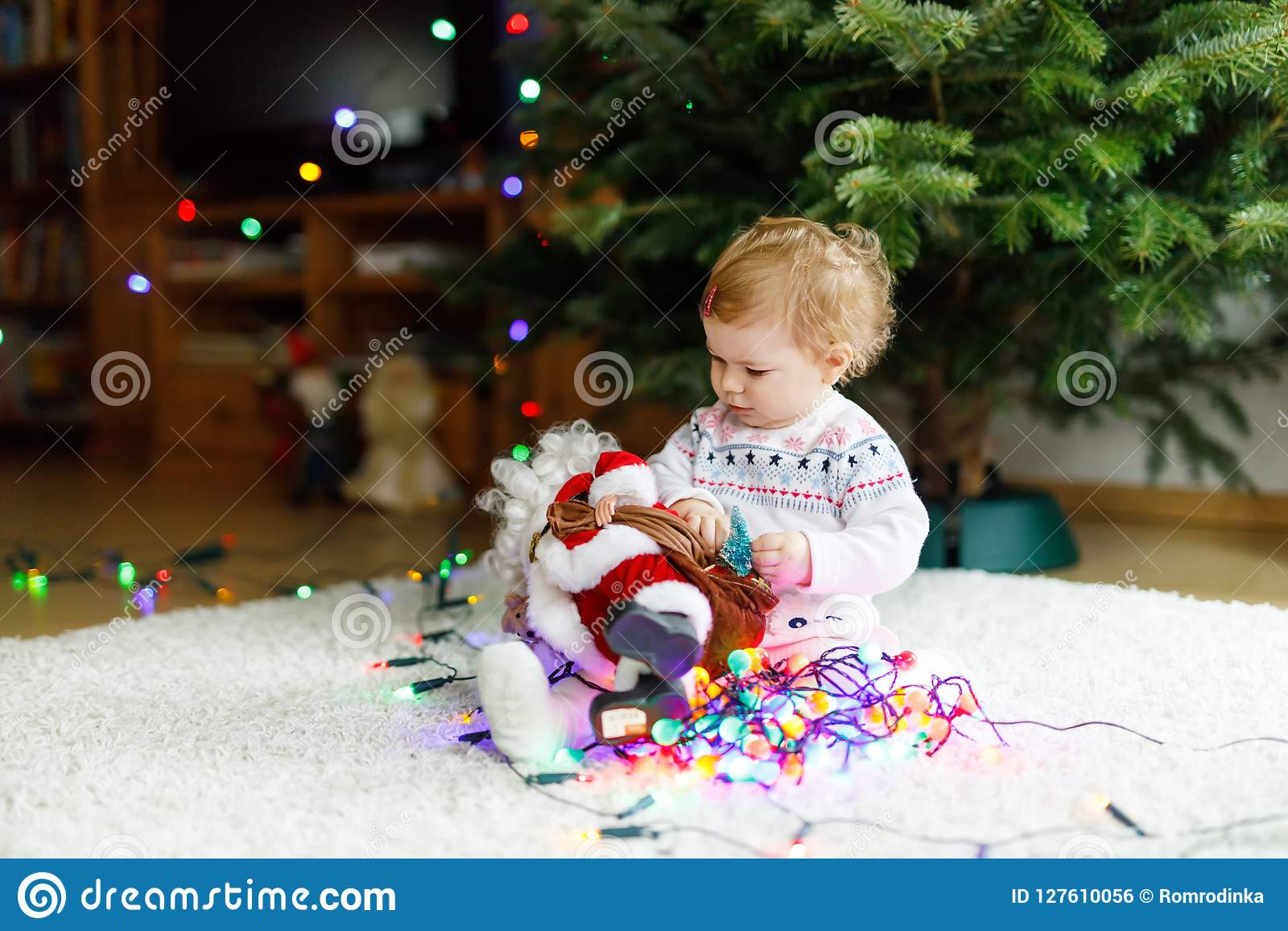 8ef4774cc Adorable baby girl holding colorful lights garland and toy Santa Claus in  cute hands.
