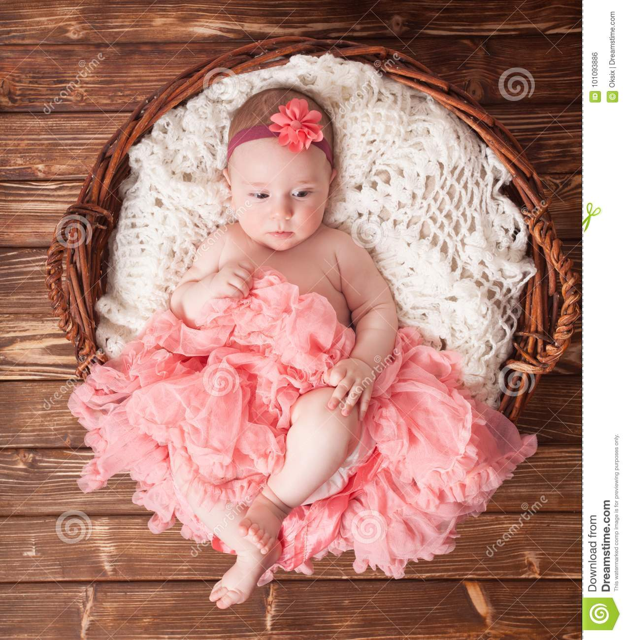 Adorable baby girl in pink tutu lying in the basket newborn photography