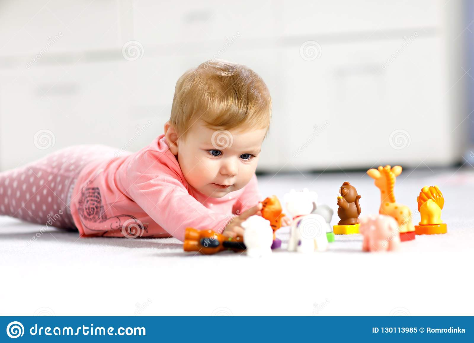 Adorable baby girl playing with domestic toy pets like cow, horse, sheep, dog and wild animals like giraffe, elephant