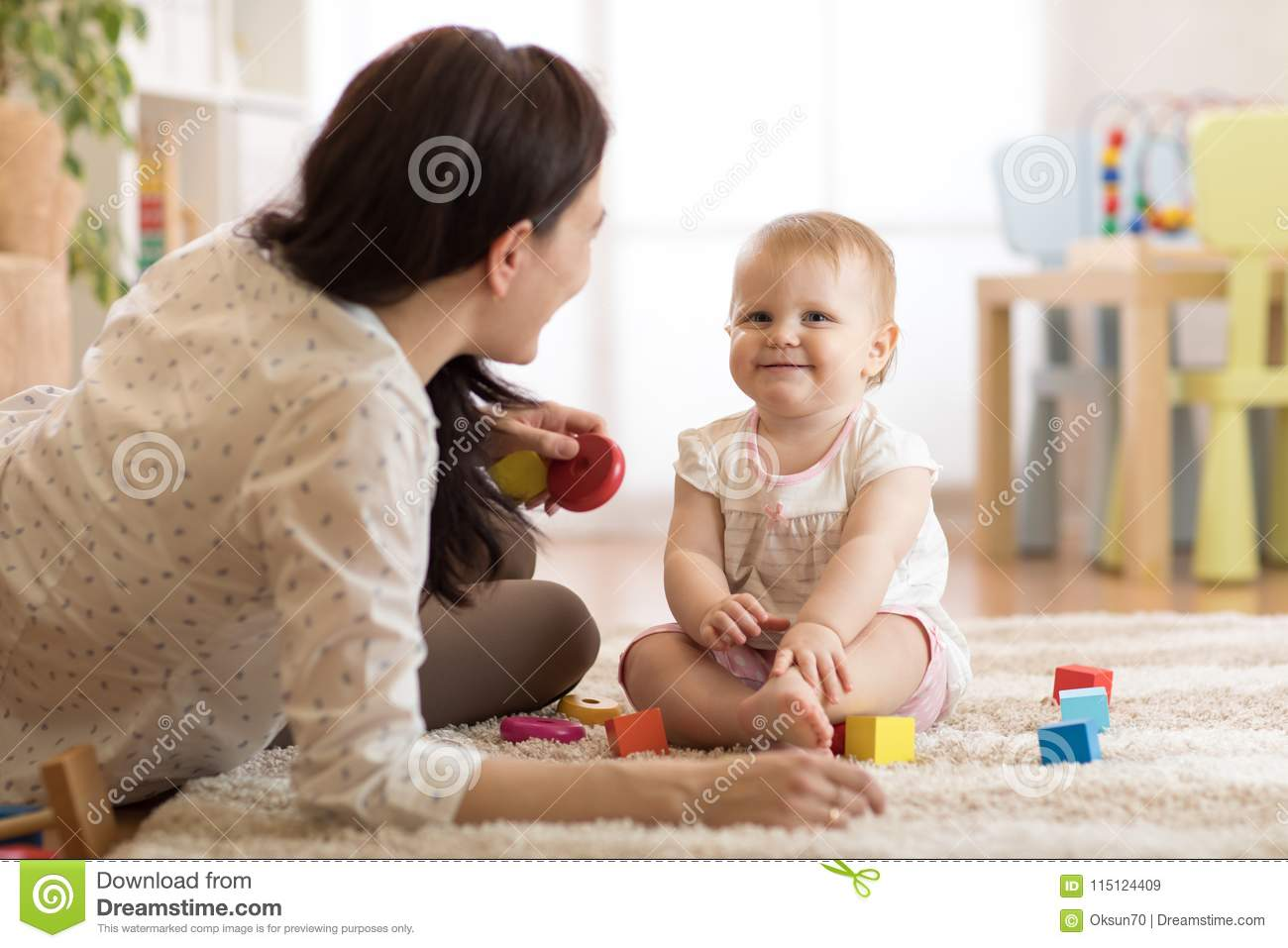 Adorable baby girl playing with educational toys in nursery. Child having fun with colorful different toys at home