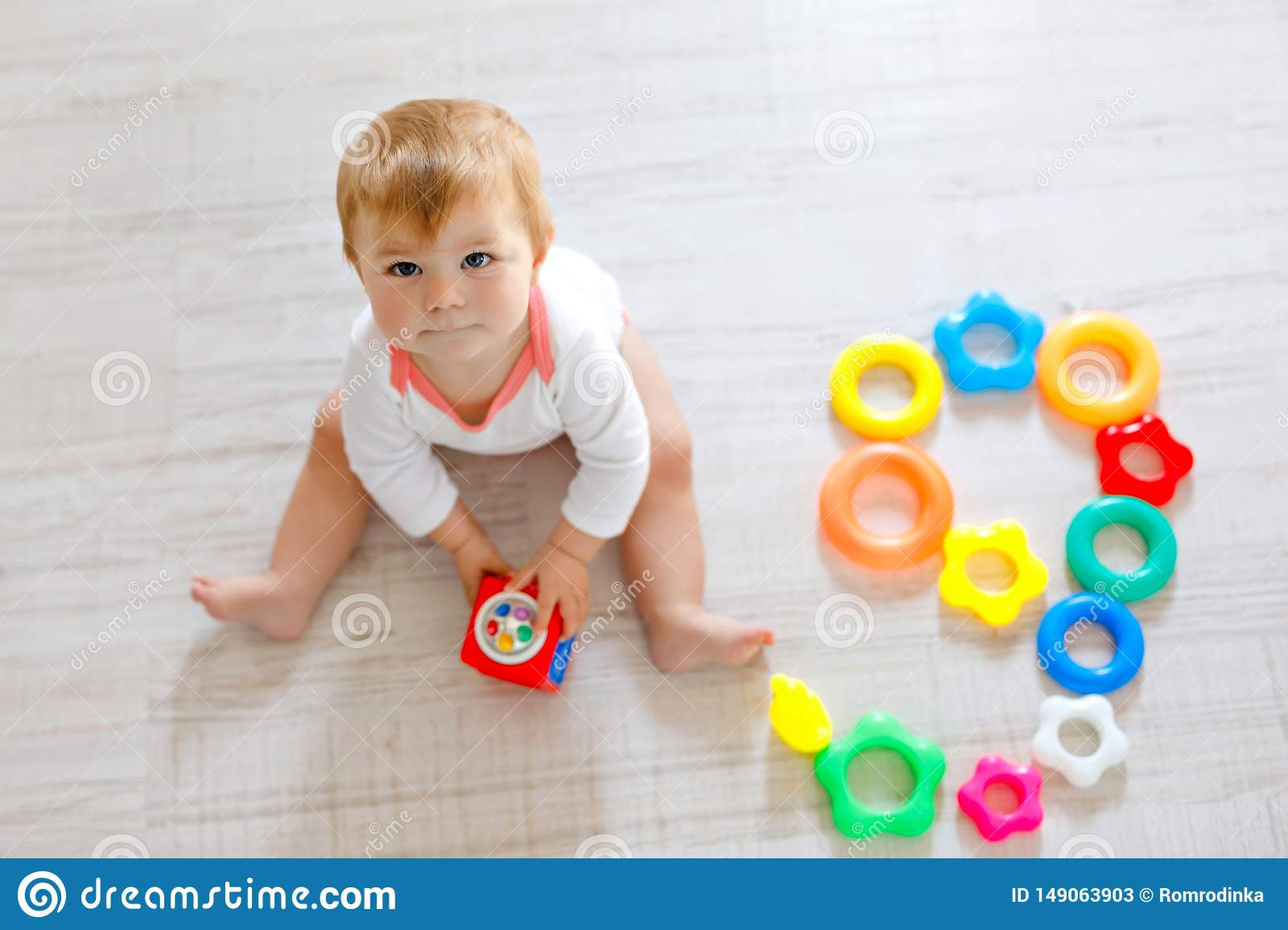 Adorable baby girl playing with educational toys in nursery. Happy healthy child having fun with colorful different toys