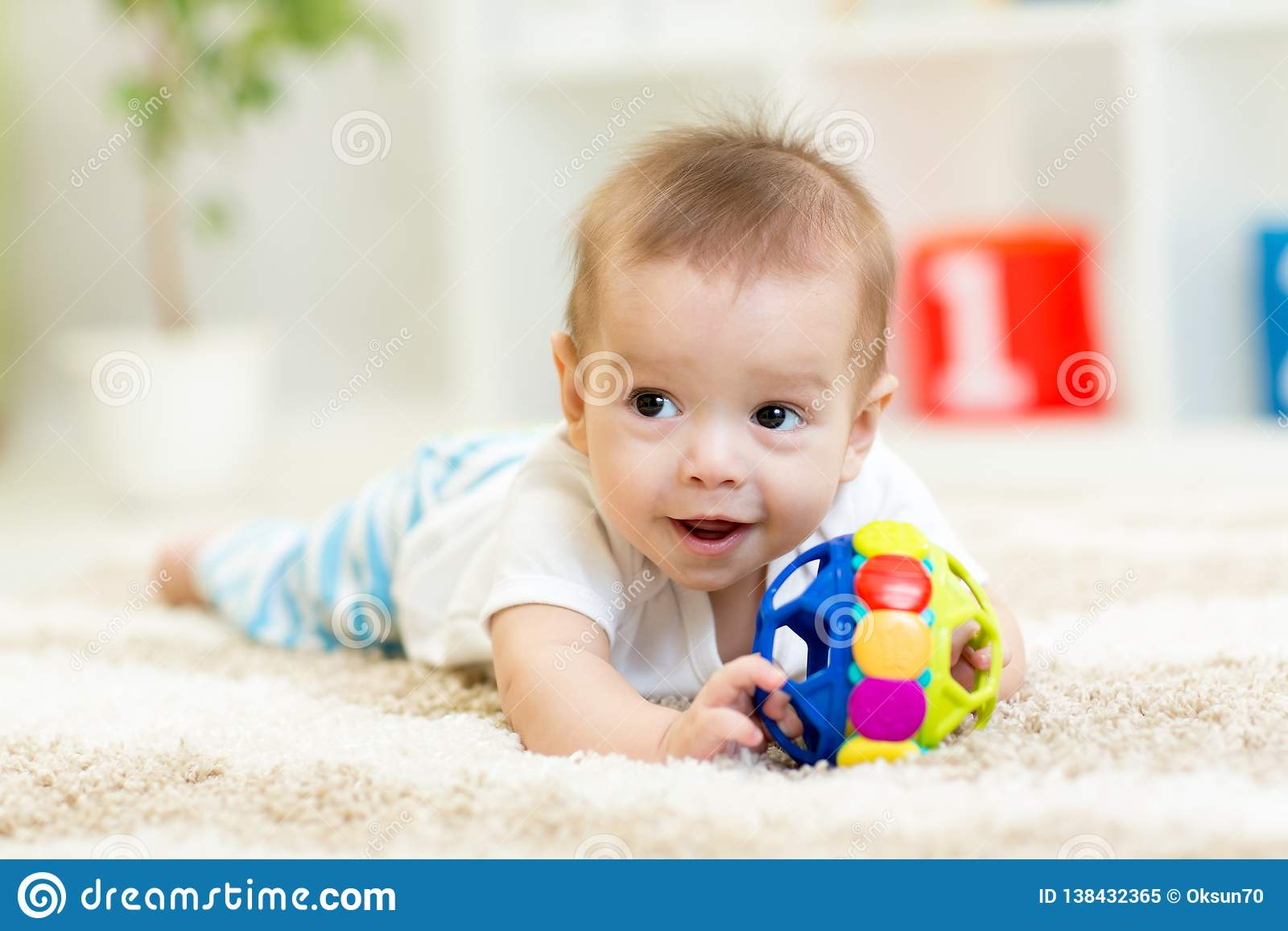 Adorable baby having fun with toy on cozy rug. Happy cheerful kid playing on the floor