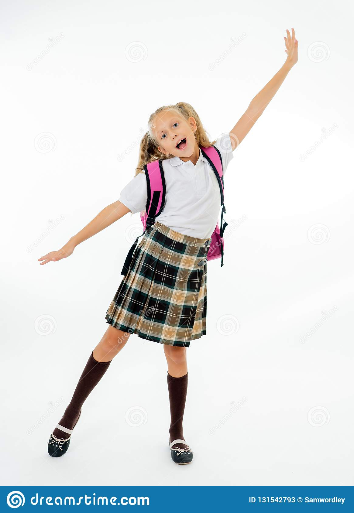 Adorable beautiful little schoolgirl with big pink schoolbag feeling excited and happy being back to school isolated on white