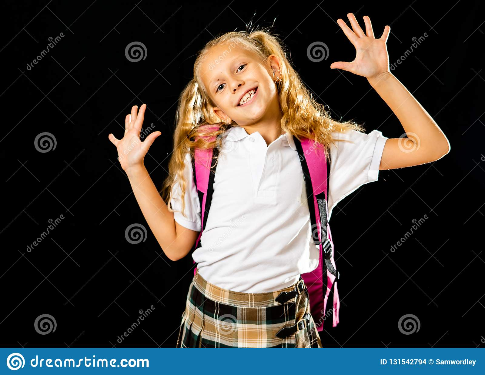 Adorable beautiful little schoolgirl with big pink schoolbag feeling excited and happy isolated on a black background in back to