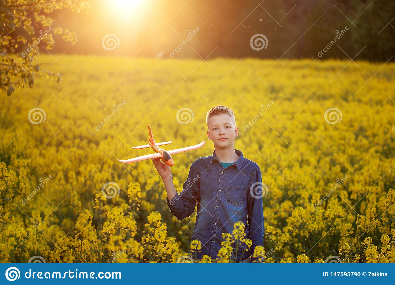 Adorable Boy holds toy plane in his hand on sunset in summer day