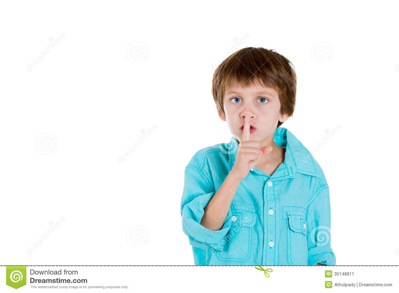 adorable boy placing finger on lips and saying shh stock