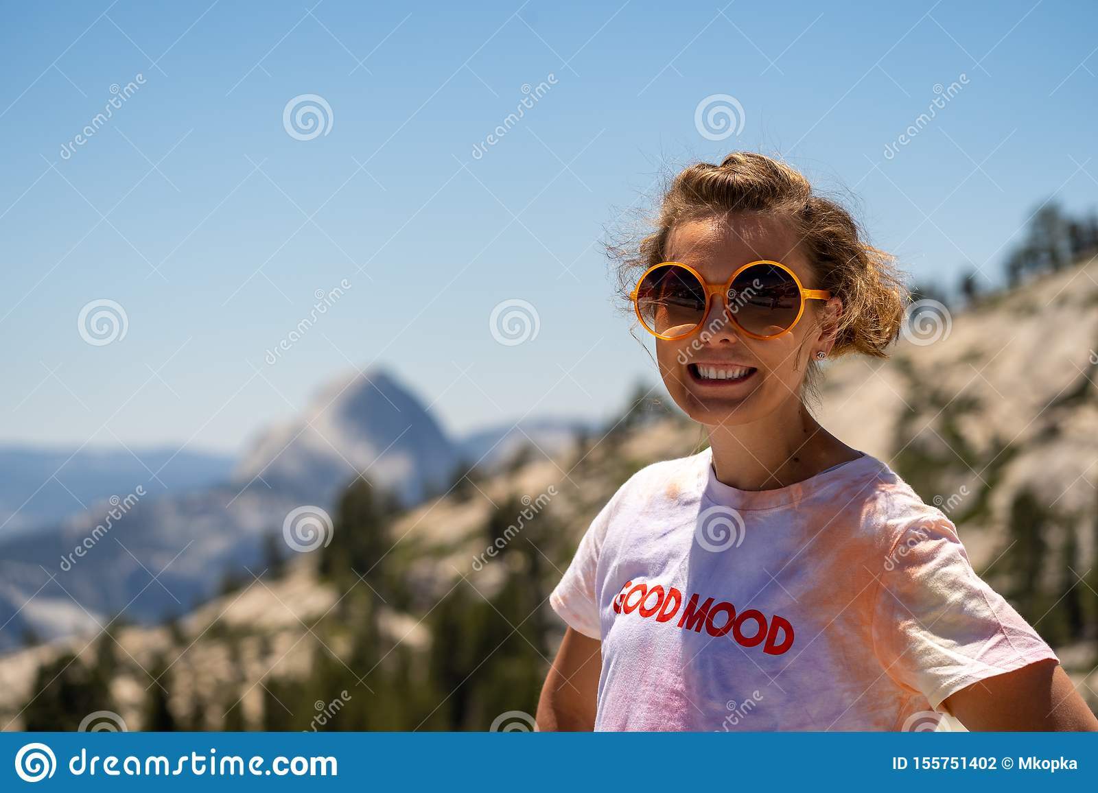 Adorable brunette young woman poses at Olmstead Point in Yosemite National Park. Half dome blurred in background