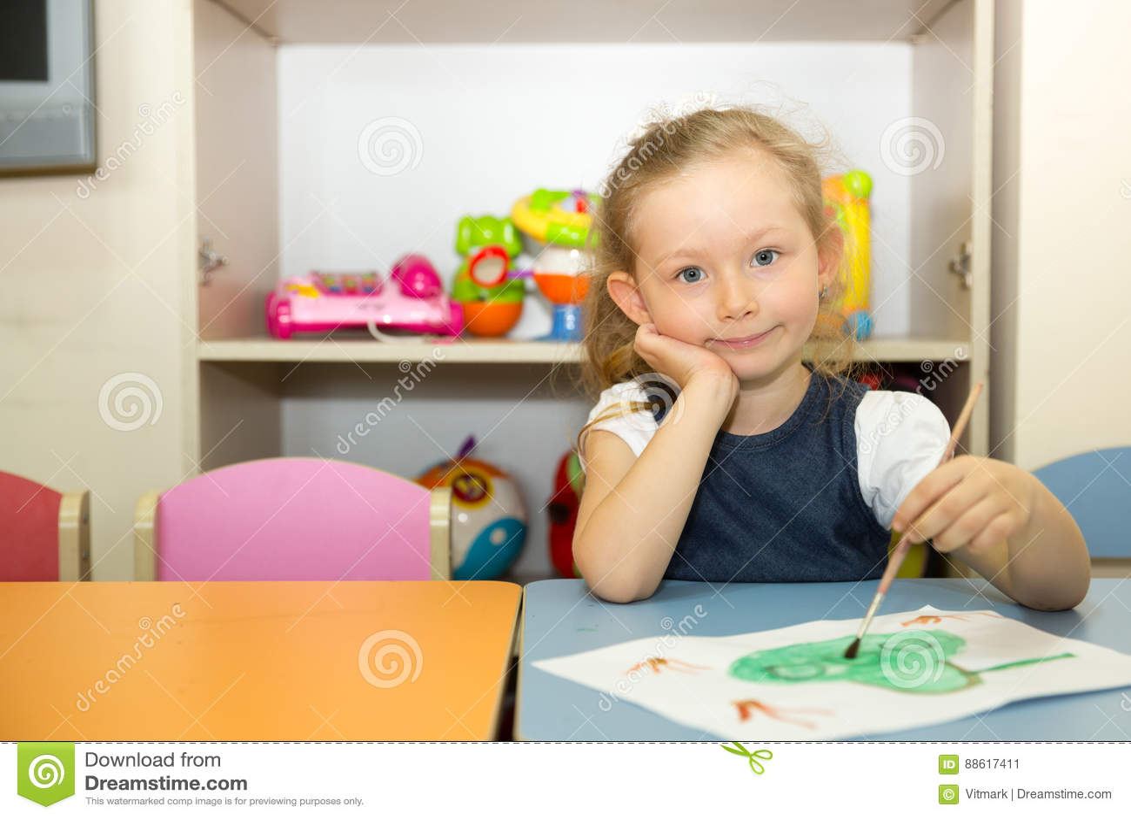 Adorable child girl draws a brush and paints in nursery room. Kid in kindergarten in Montessori preschool class.