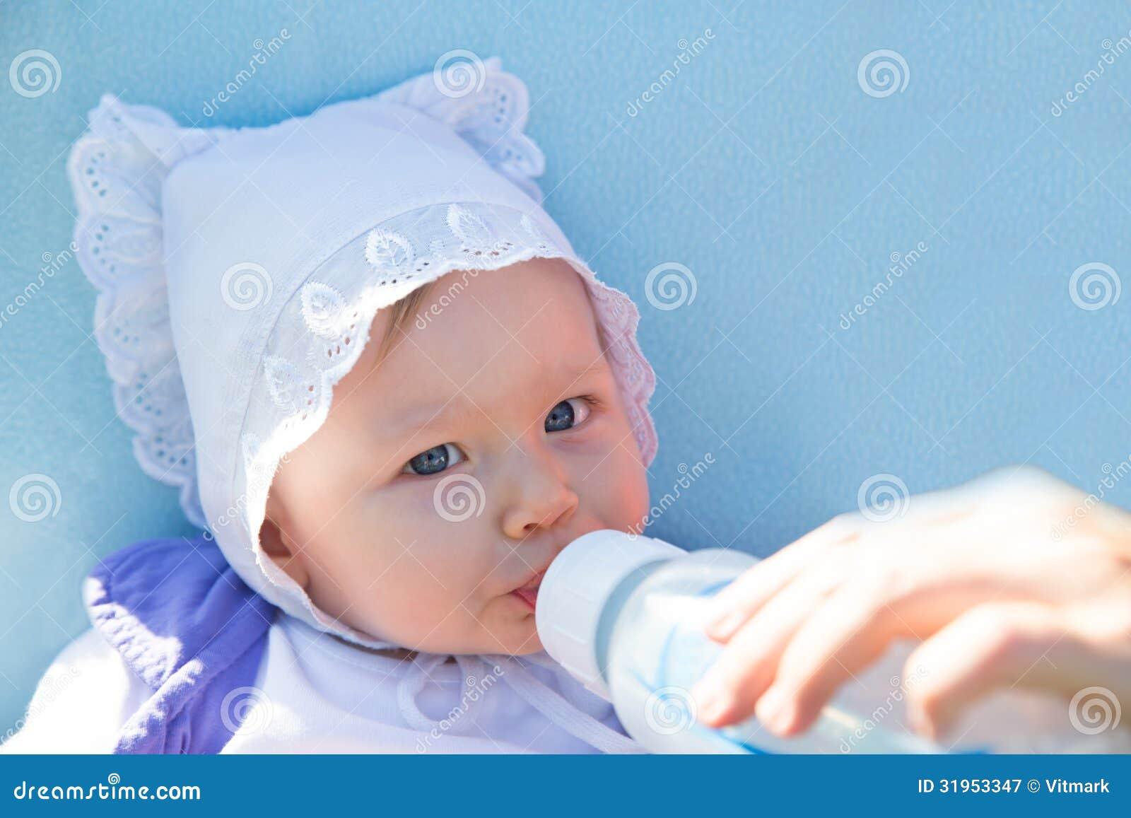 Adorable child girl with infant formula in bottle drinking milk