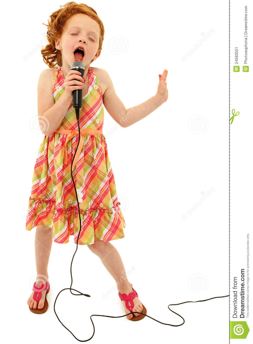 Adorable elementary age school girl singing into microphone isolated ...