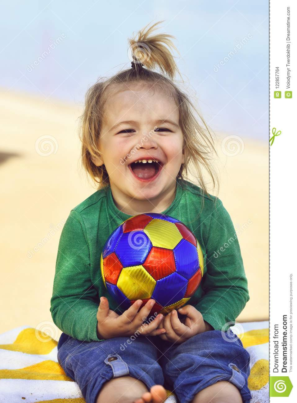 Adorable boy small child with happy smiling face holding ball