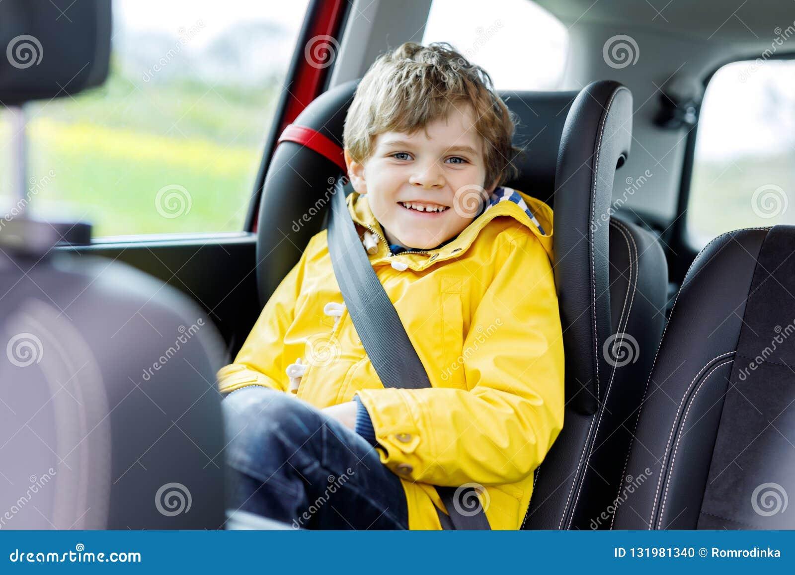 057998b46 Adorable cute preschool kid boy sitting in car in yellow rain coat. Little  school child
