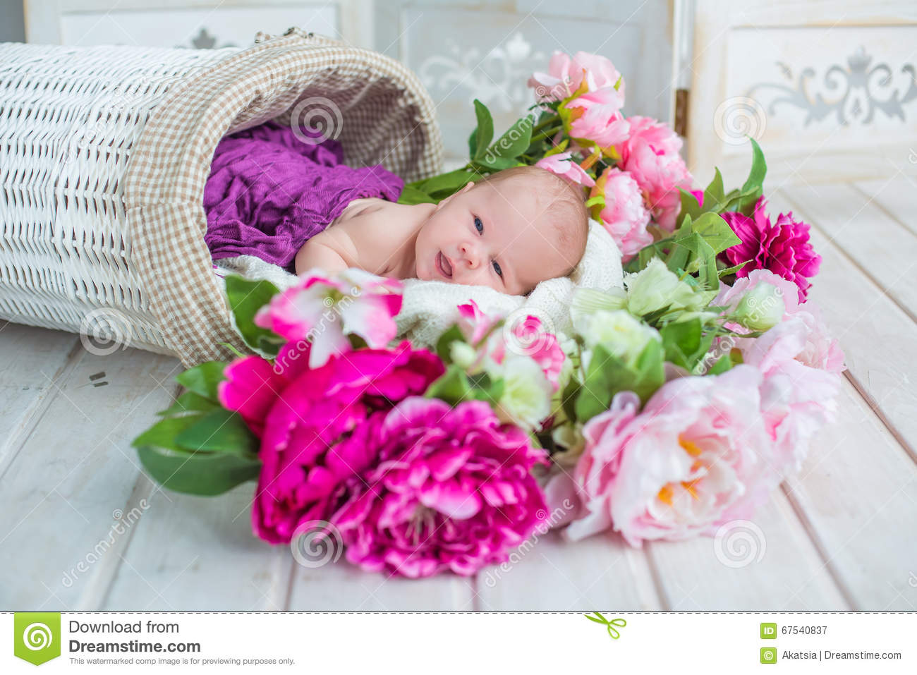 adorable cute sweet baby girl in white basket with flowers on wooden