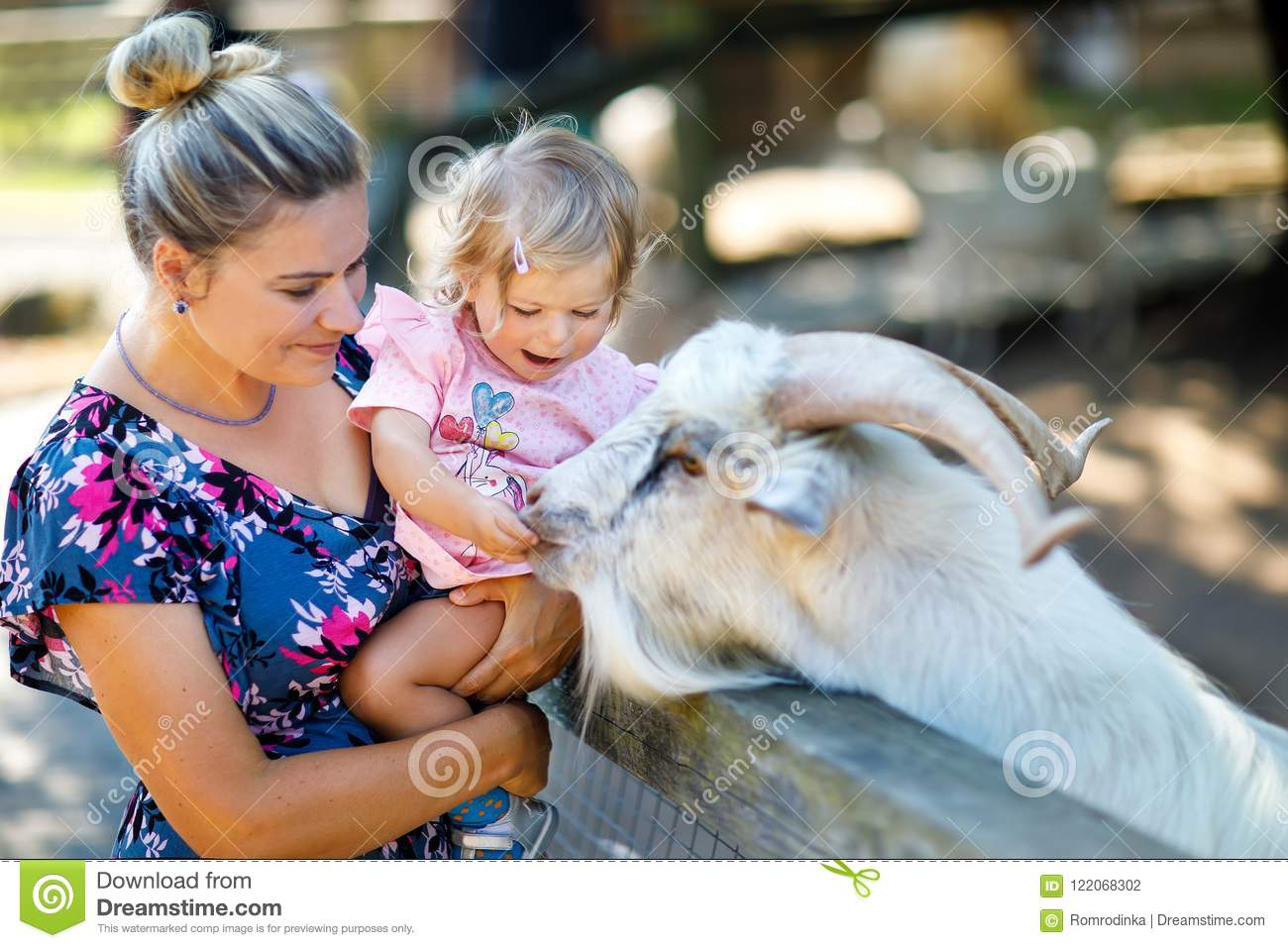 Adorable cute toddler girl and young mother feeding little goats and sheeps on a kids farm. Beautiful baby child petting