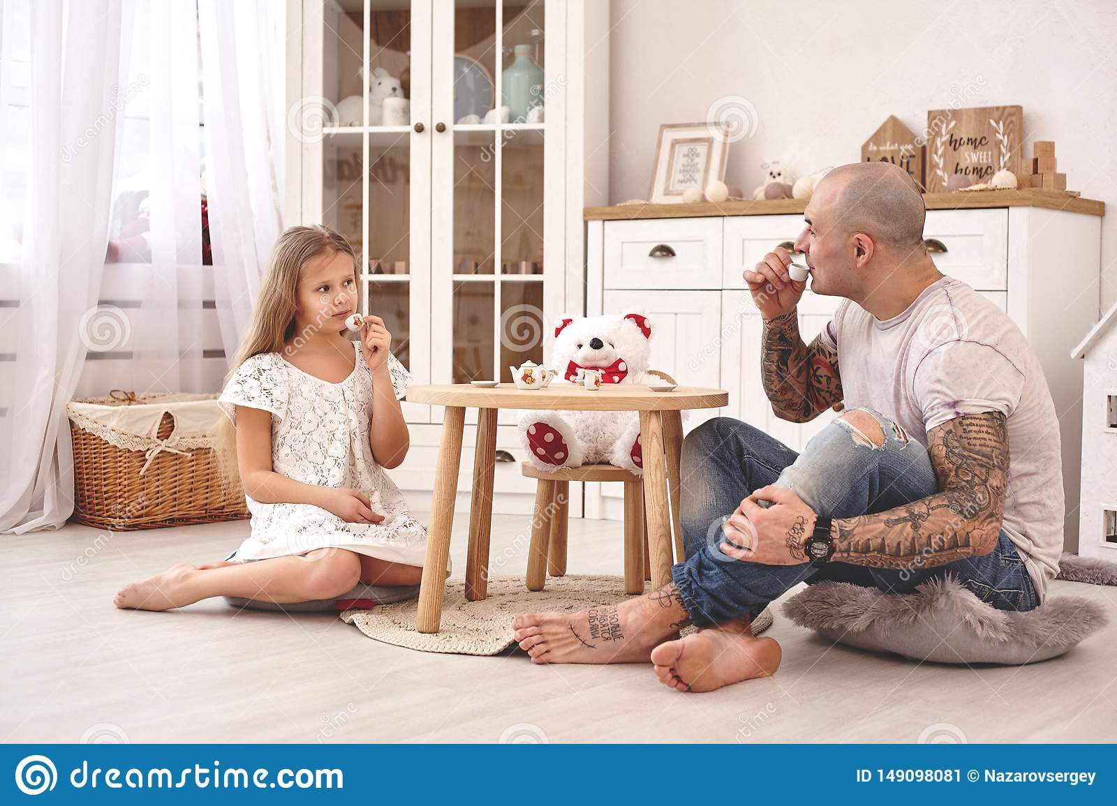 Adorable daughter wearing a white dress whith her loving father. They are drinking tea from a toy dishes in a modern kid