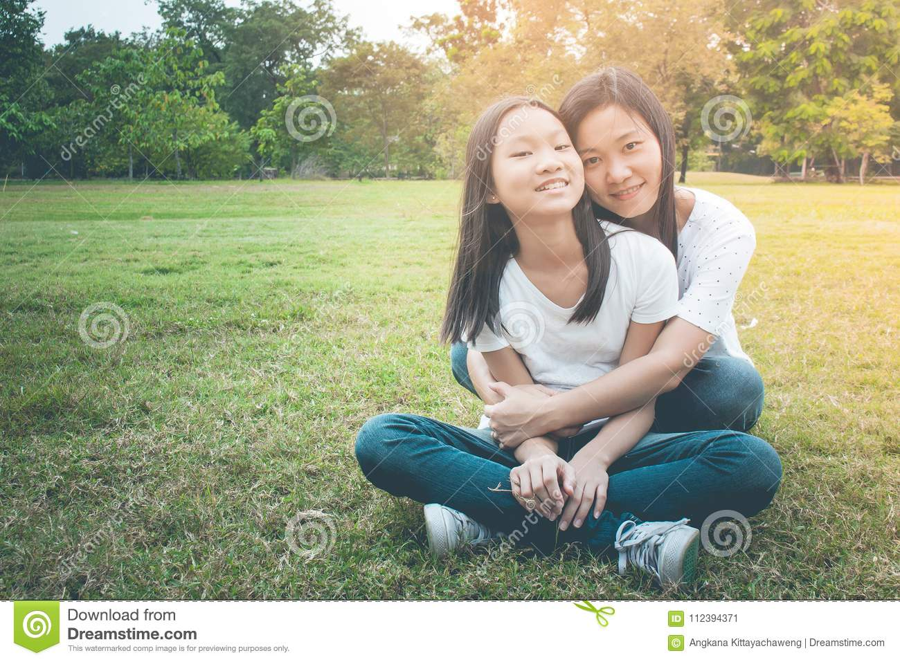 Adorable and Family Concept : Woman and child sitting relax on green grass. They hugging and feeling smiling happiness.