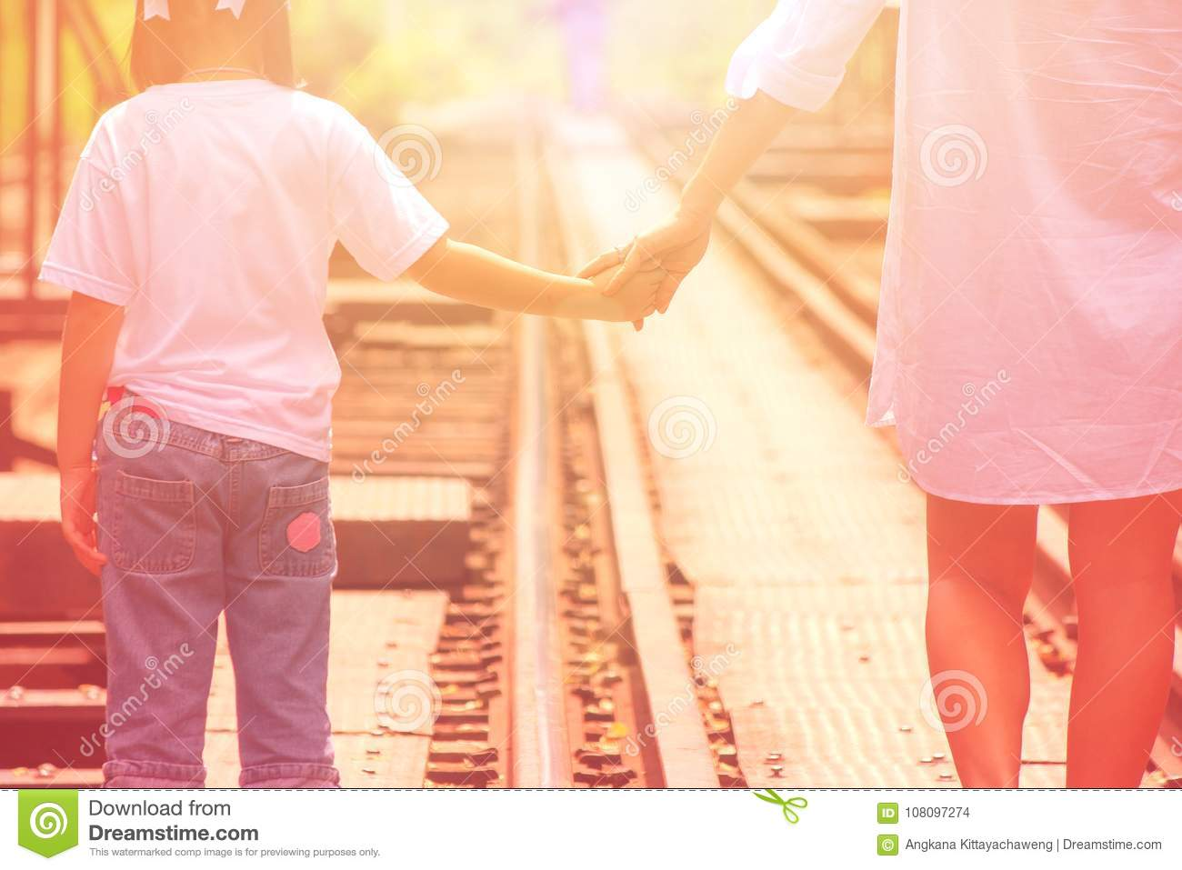 Adorable Family Concept : Woman and children walking on railroad tracks and holding hand together with looking to forward.