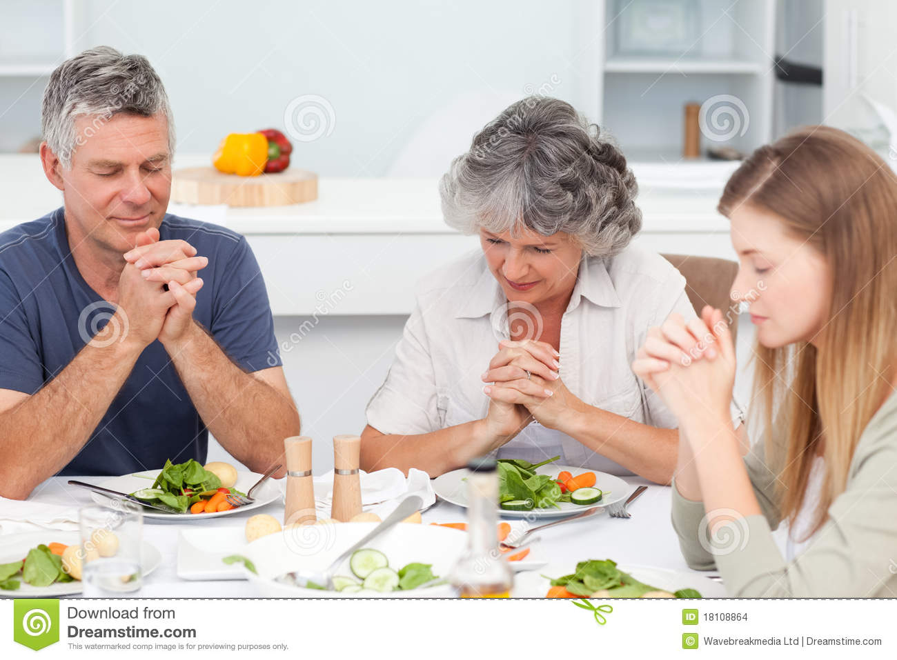 Adorable family praying at the table