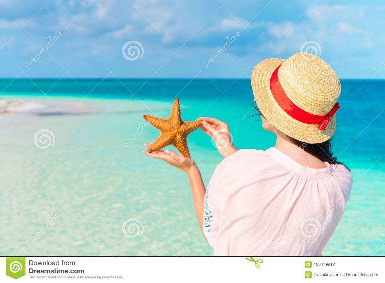 Rear view of young woman with starfish on white beach in the nature reserve