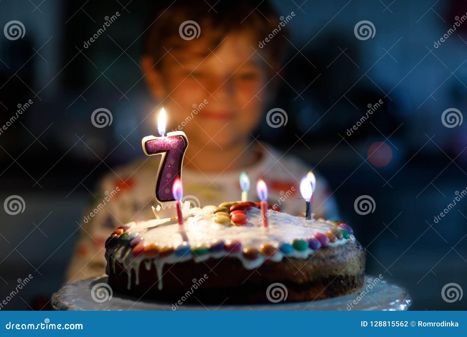 Adorable happy blond little kid boy celebrating his 7 birthday.