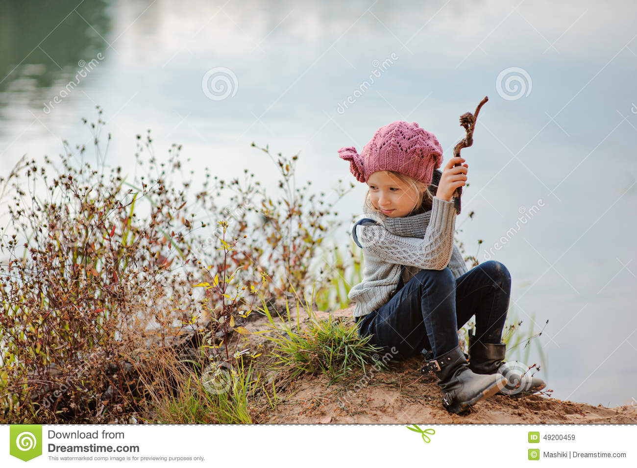 Adorable happy child girl plays with stick on river side in sunny day