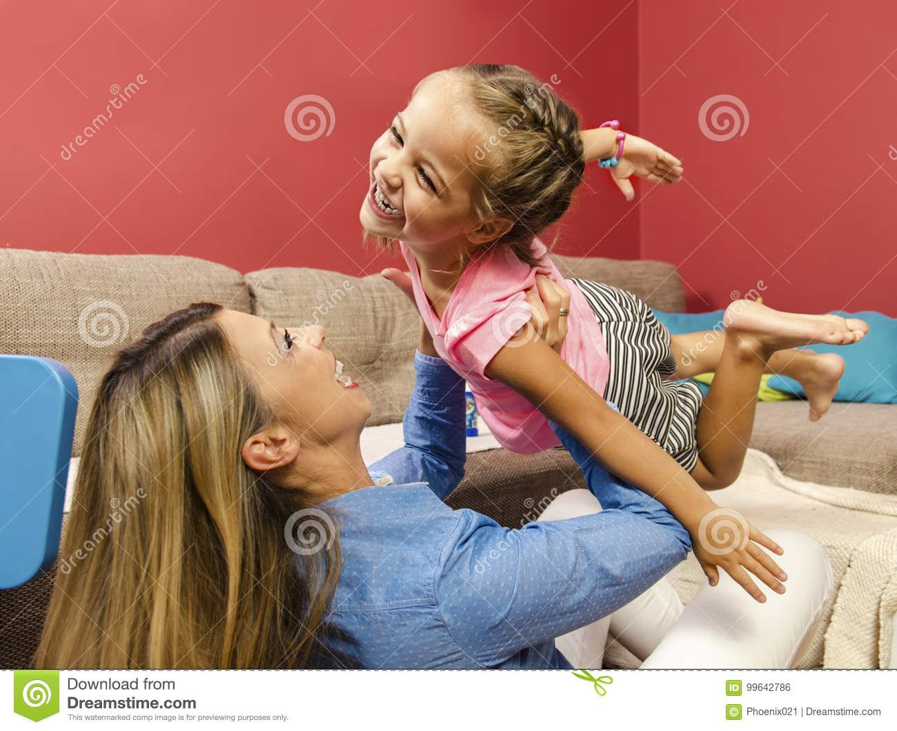 Adorable happy little girl flying throw air in her mothers arms