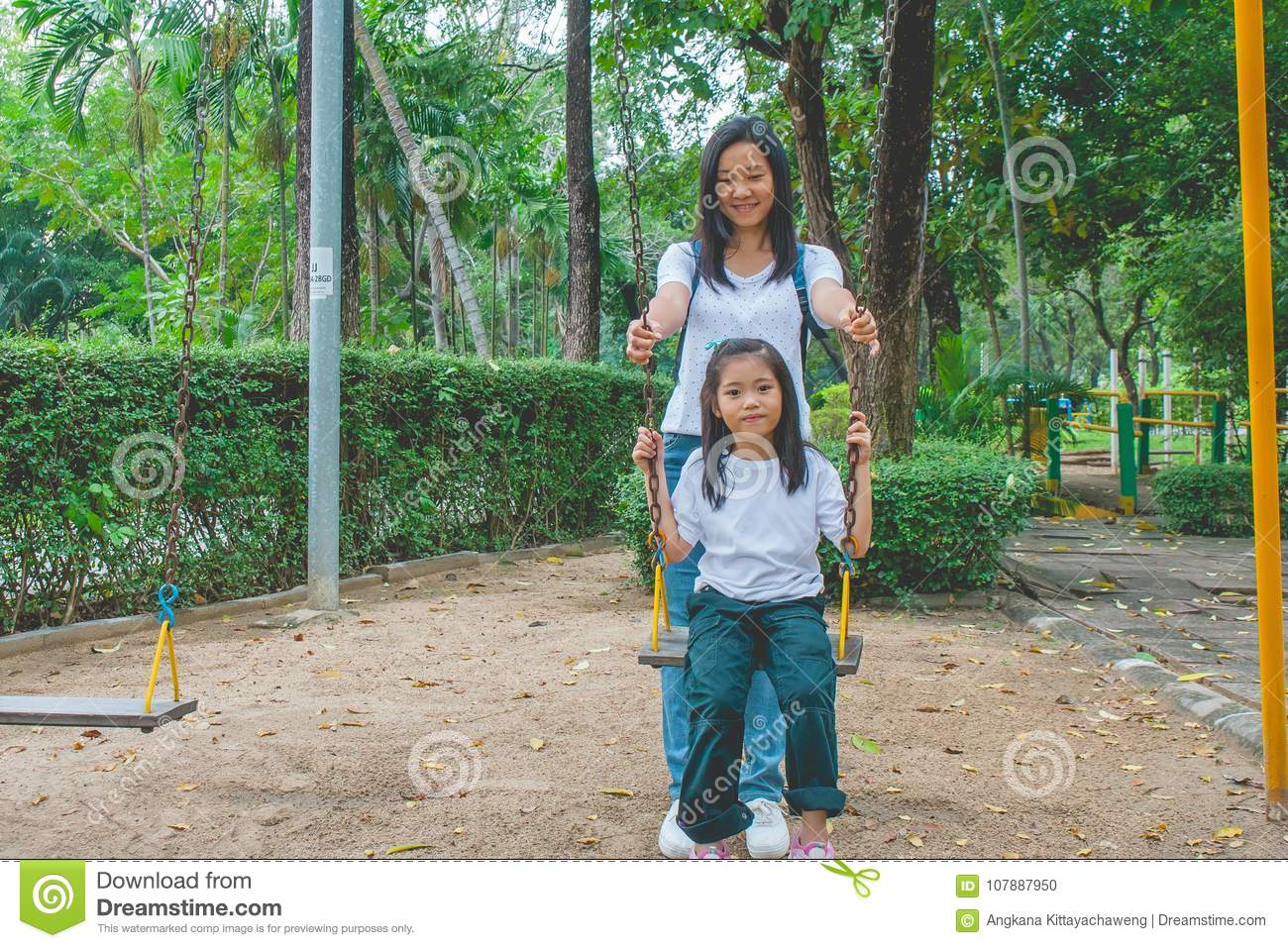 Adorable and Holiday Concept : Woman and child feeling funny and happiness on a swing at playground.