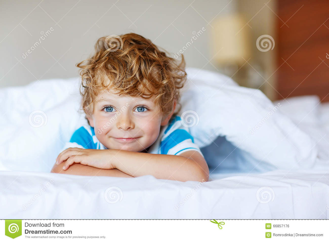 Adorable kid boy after sleeping in his white bed