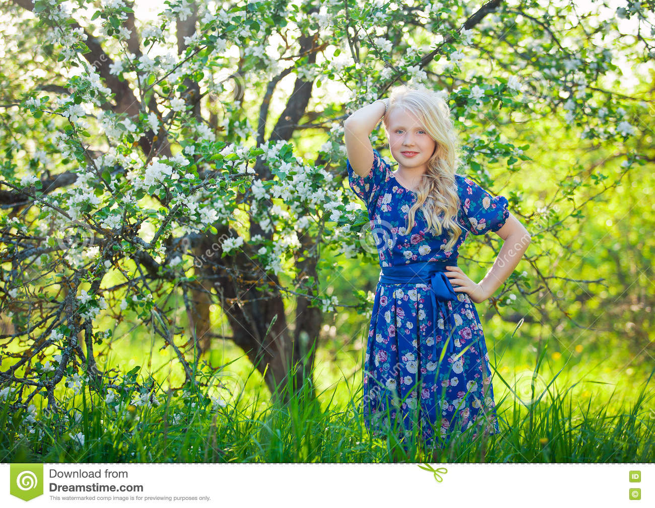 Adorable kid playing in nature. Cute little child, blonde toddler girl playing in blooming cherry garden on beautiful