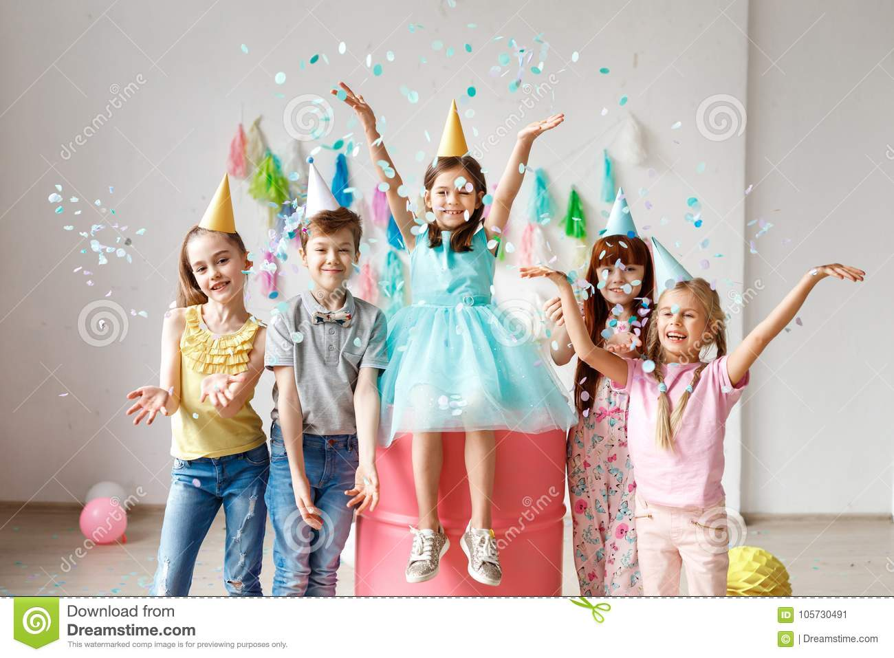 Adorable kids have fun together, throw colourful confetti, wears cone hats, have fun at birthday party, play together in