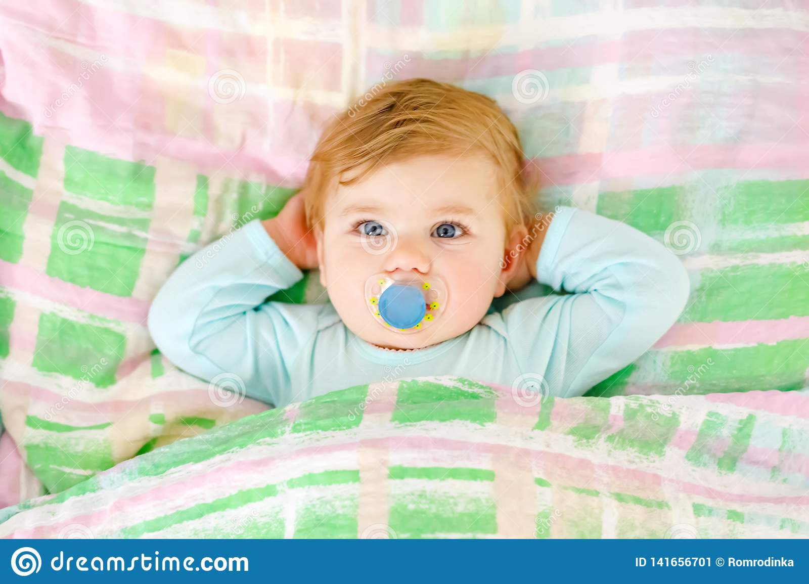 Adorable little baby girl sleeping in bed. Calm peaceful child dreaming during day sleep. Beautiful baby in parents bed