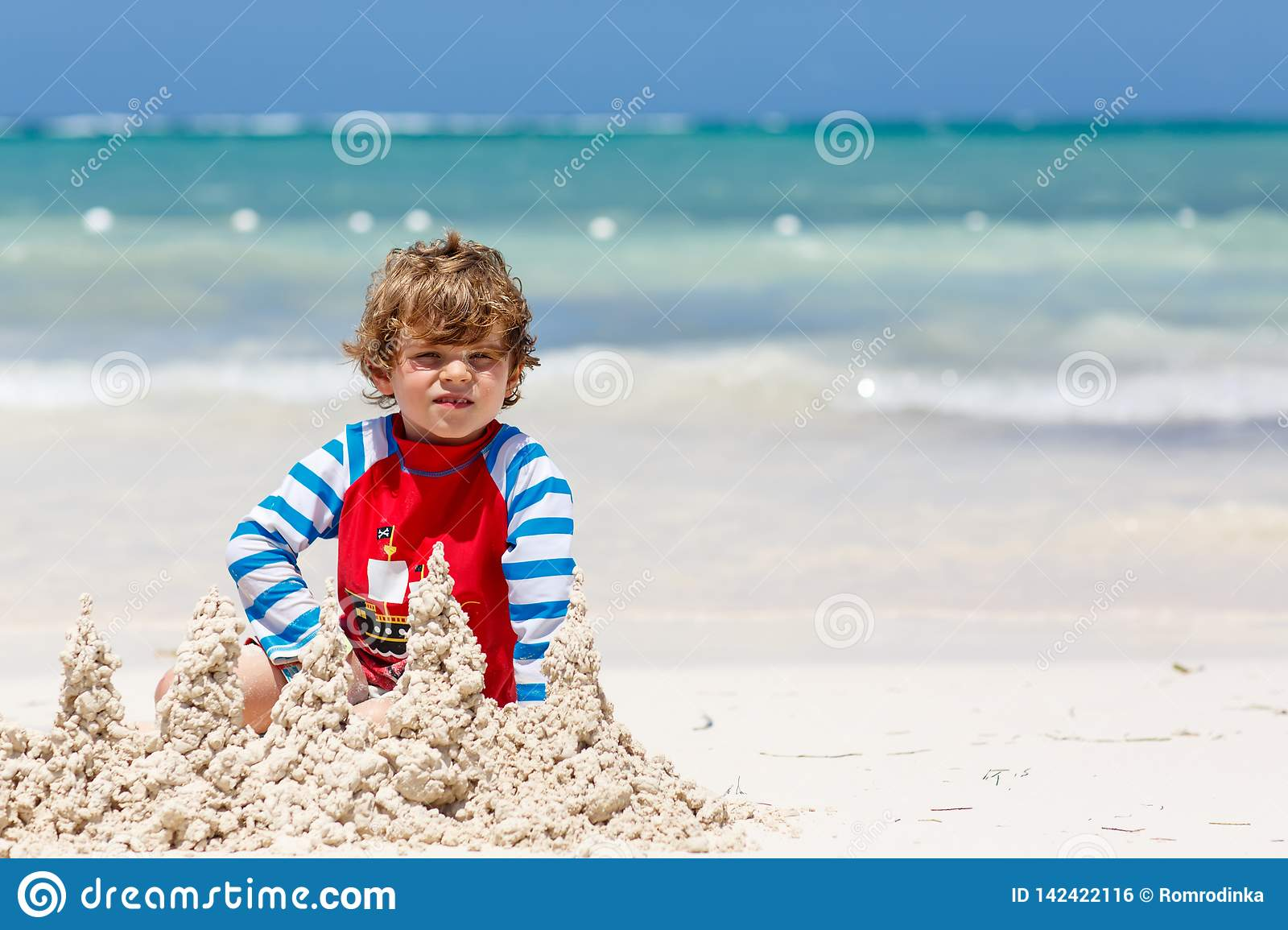 Adorable little blond kid boy having fun on tropical beach of carribean island. Excited child playing and building sand