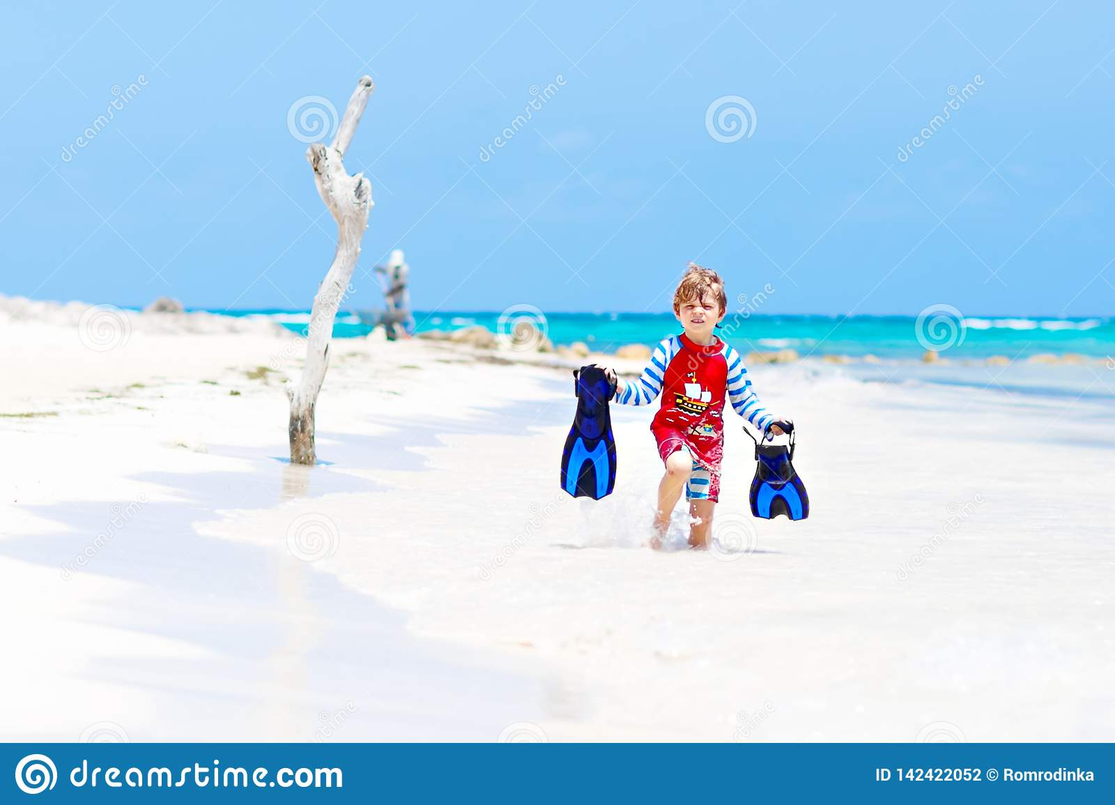 Adorable little blond kid boy having fun on tropical beach of Maldives. Excited child playing and surfing in sun
