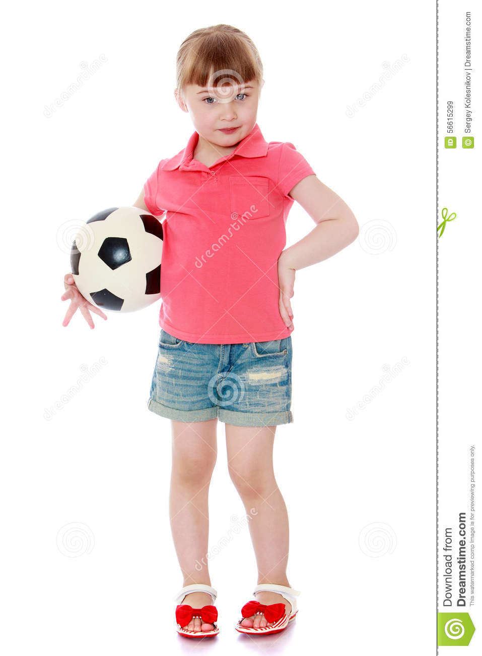 c11963bf3 Adorable little blonde girl in denim shorts and red shirt is holding under  his arm a soccer ball - isolated on white background