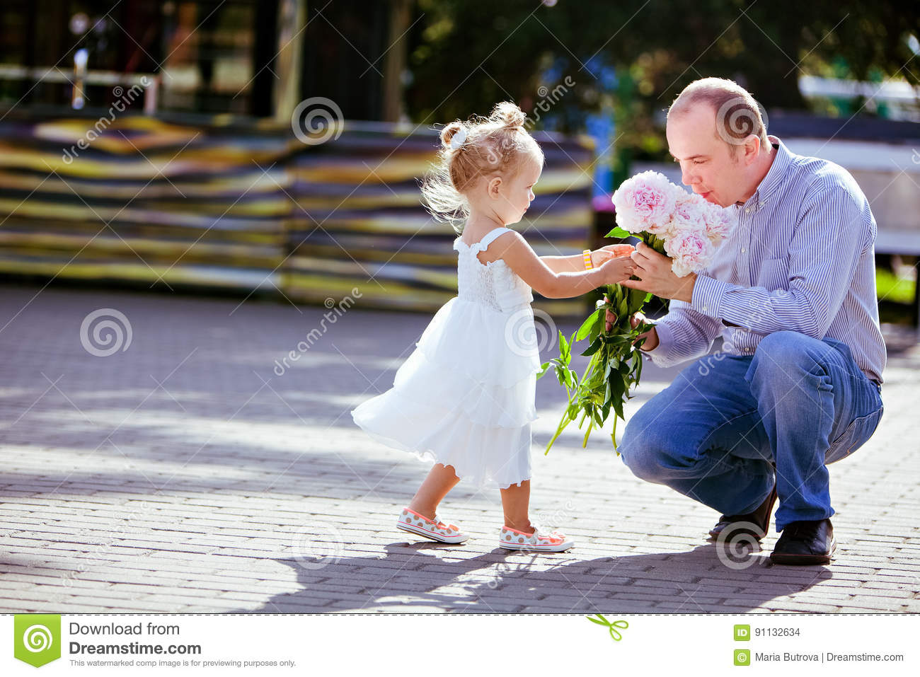 Adorable little blonde girl gives daddy peonies