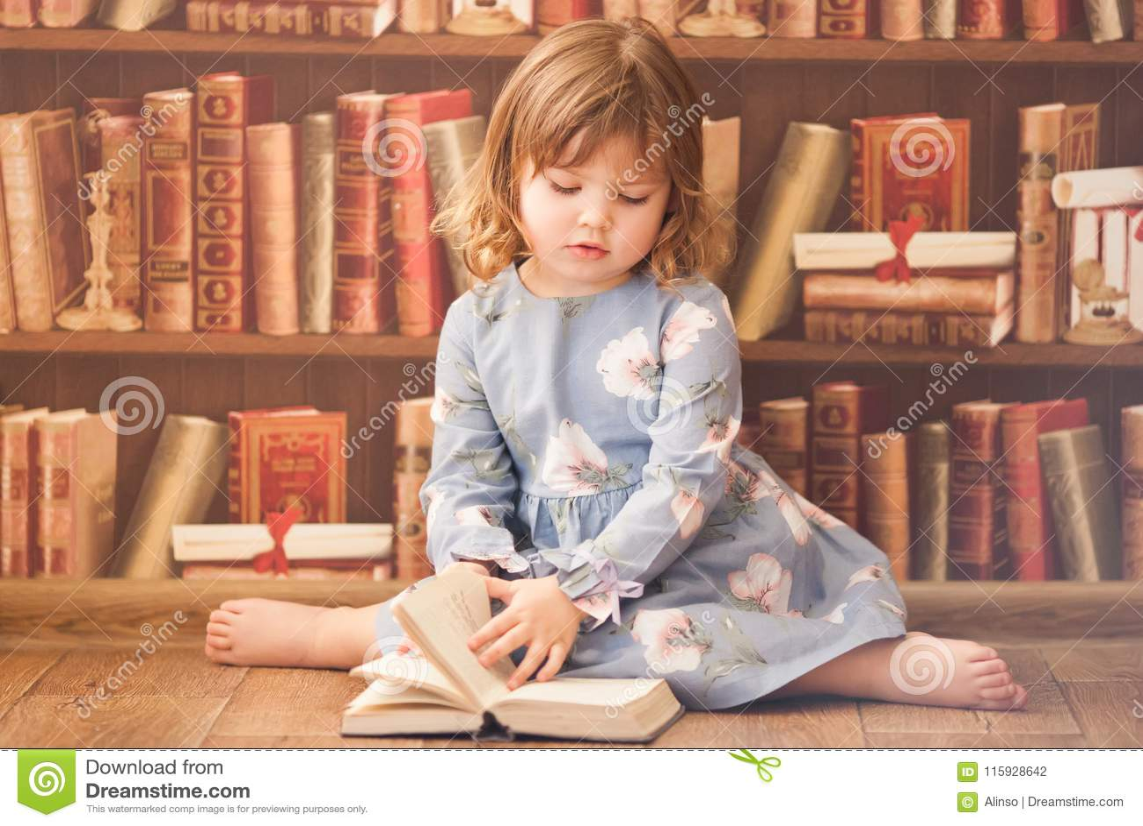 Adorable little bookworm girl reading books.