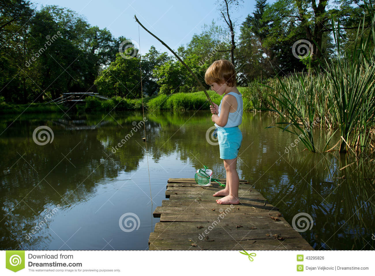 Adorable little boy fishing from wooden dock on a lake on for Little boy fishing