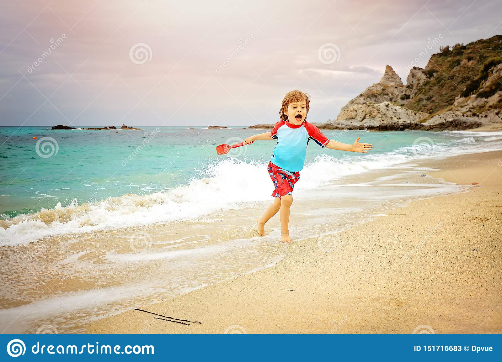 Adorable little boy having fun at the beach on vacation. Kid wearing swimming trunks and sun protection t-shot playing