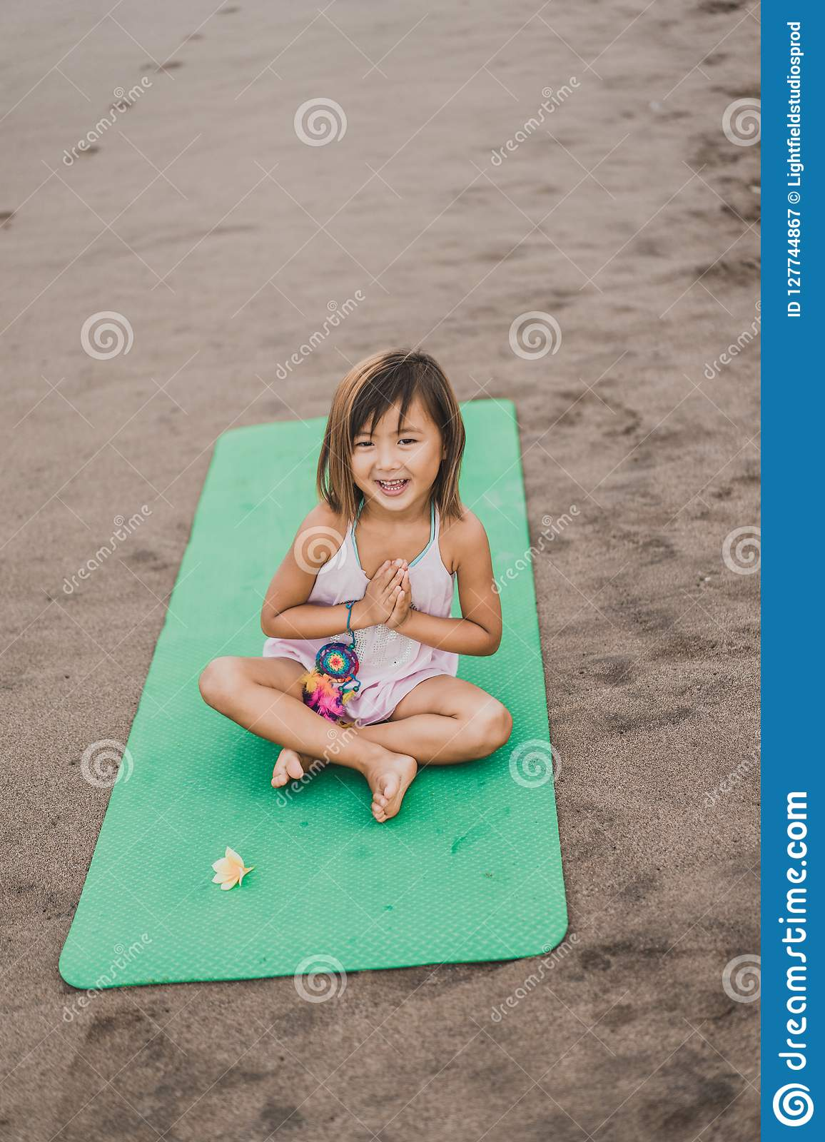 adorable little child practicing yoga on mat in lotus pose with namaste mudra