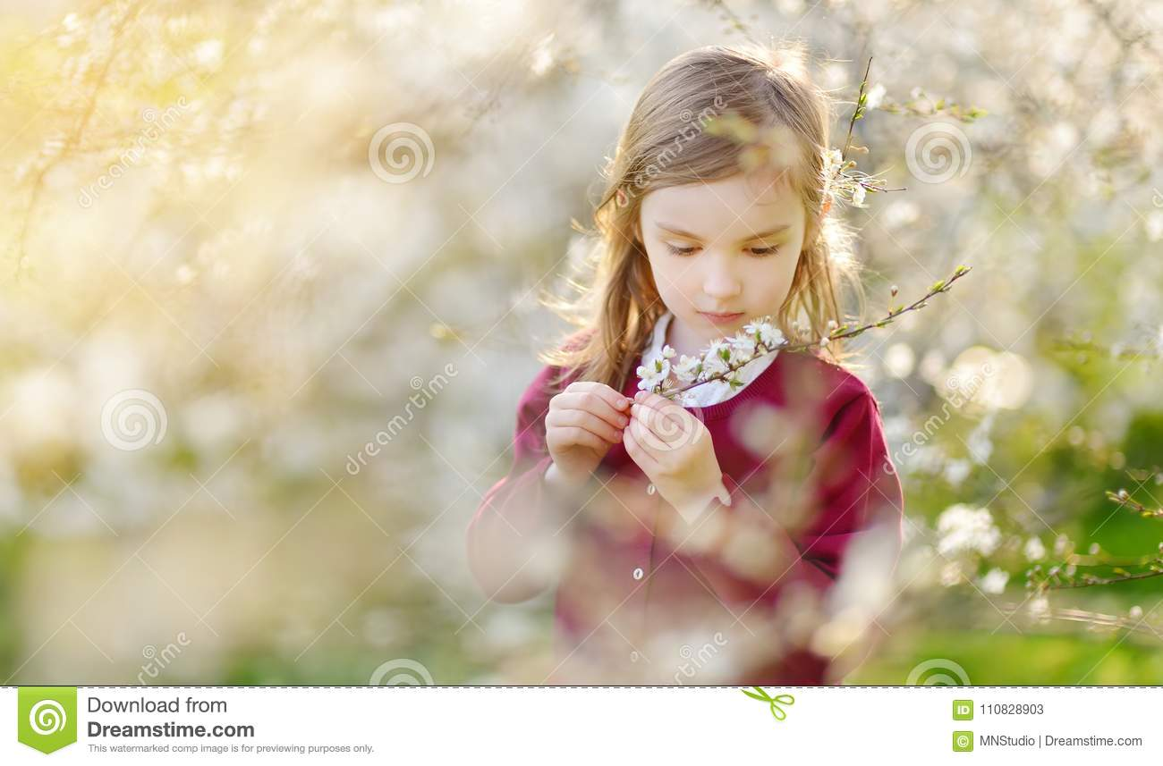 Adorable little girl in blooming cherry tree garden on beautiful spring day
