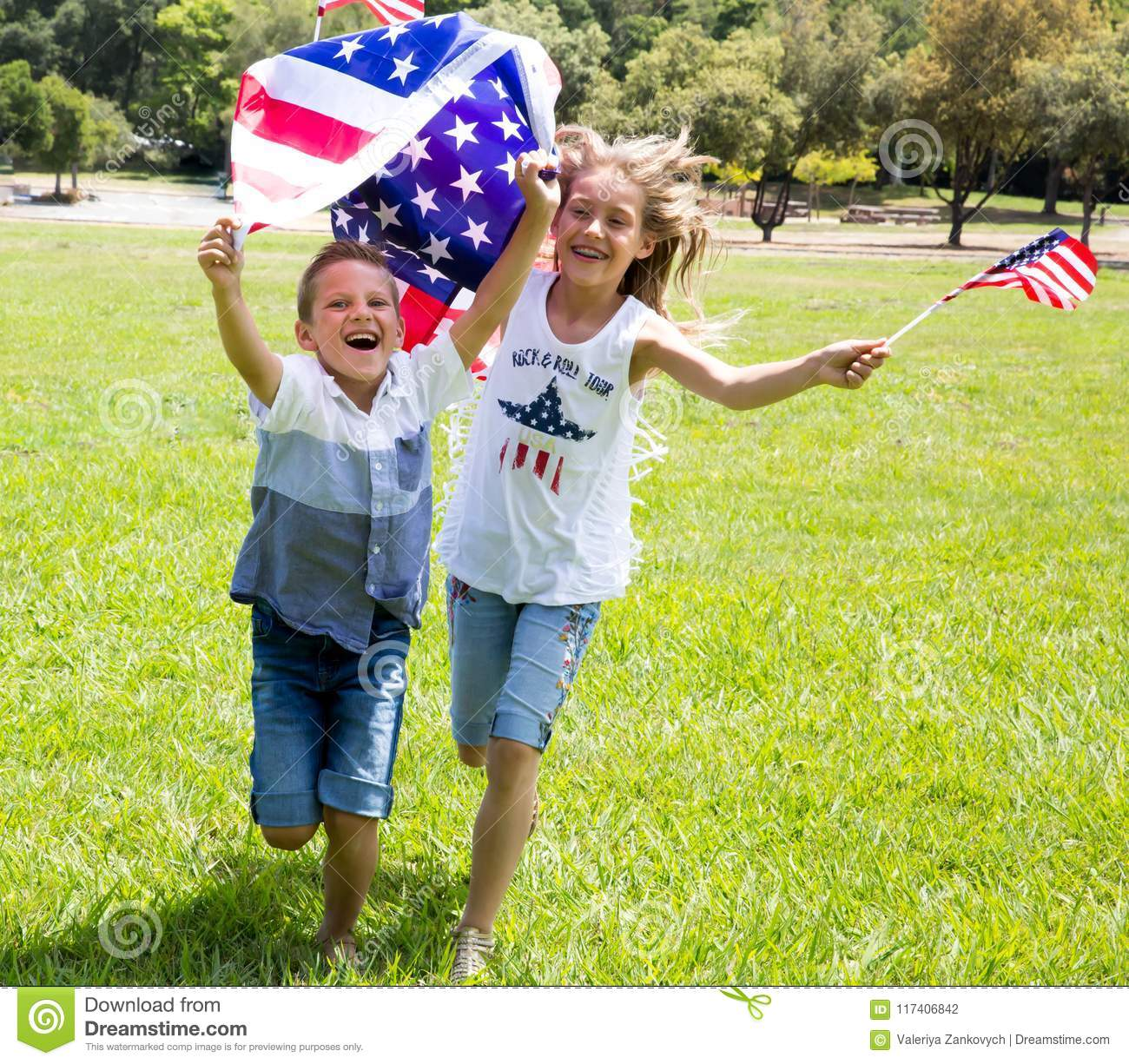 Adorable little girl and boy run on bright green grass holding american flag outdoors on Independence Day holiday