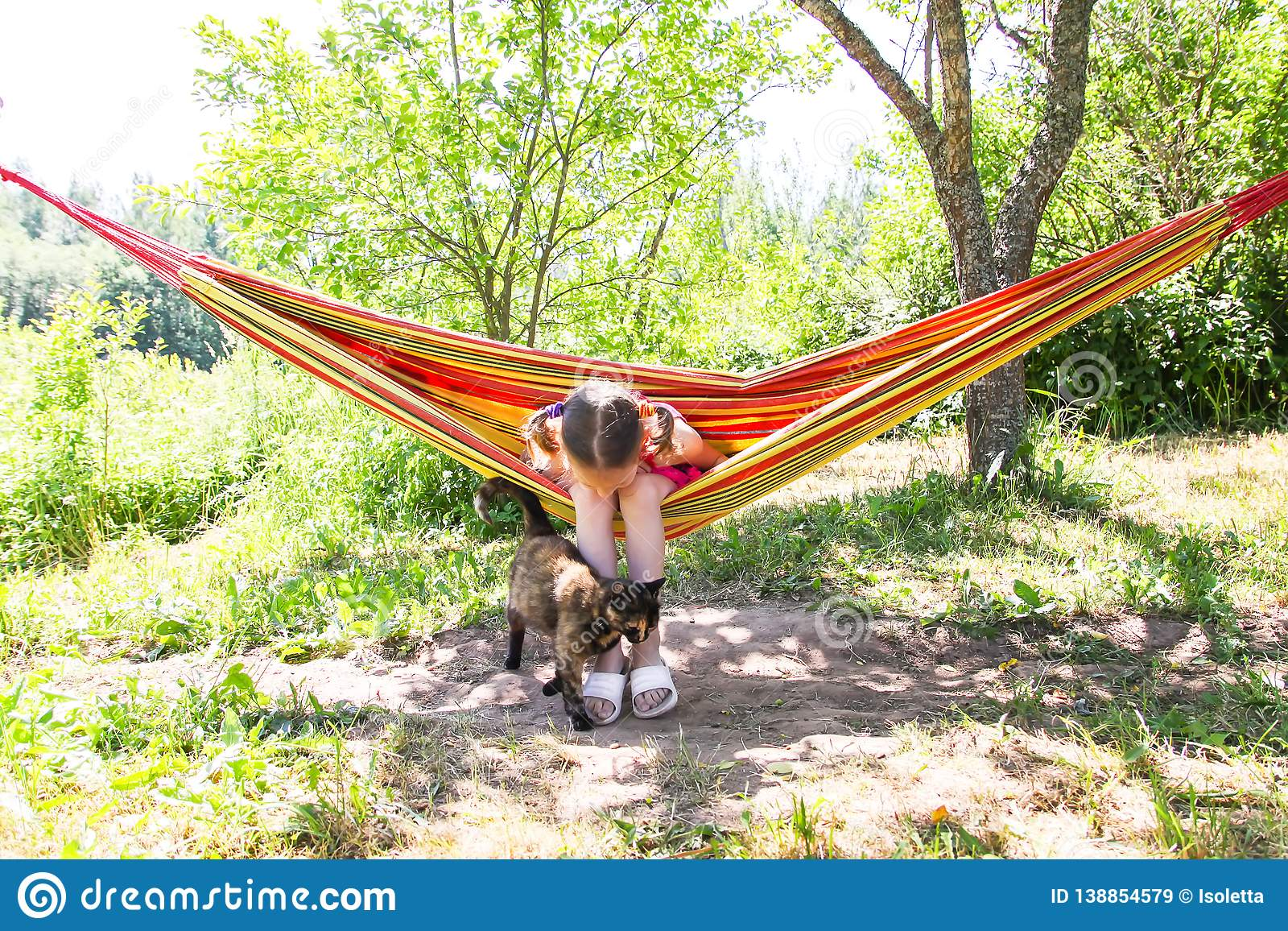 Adorable little girl with curly hair in colorful striped hammock on summer nature background in countryside