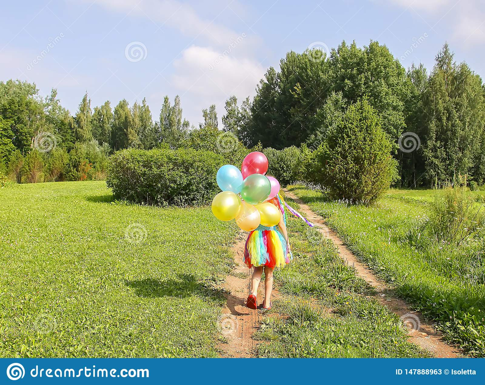 Adorable little girl on green grass with colorful bright balloons