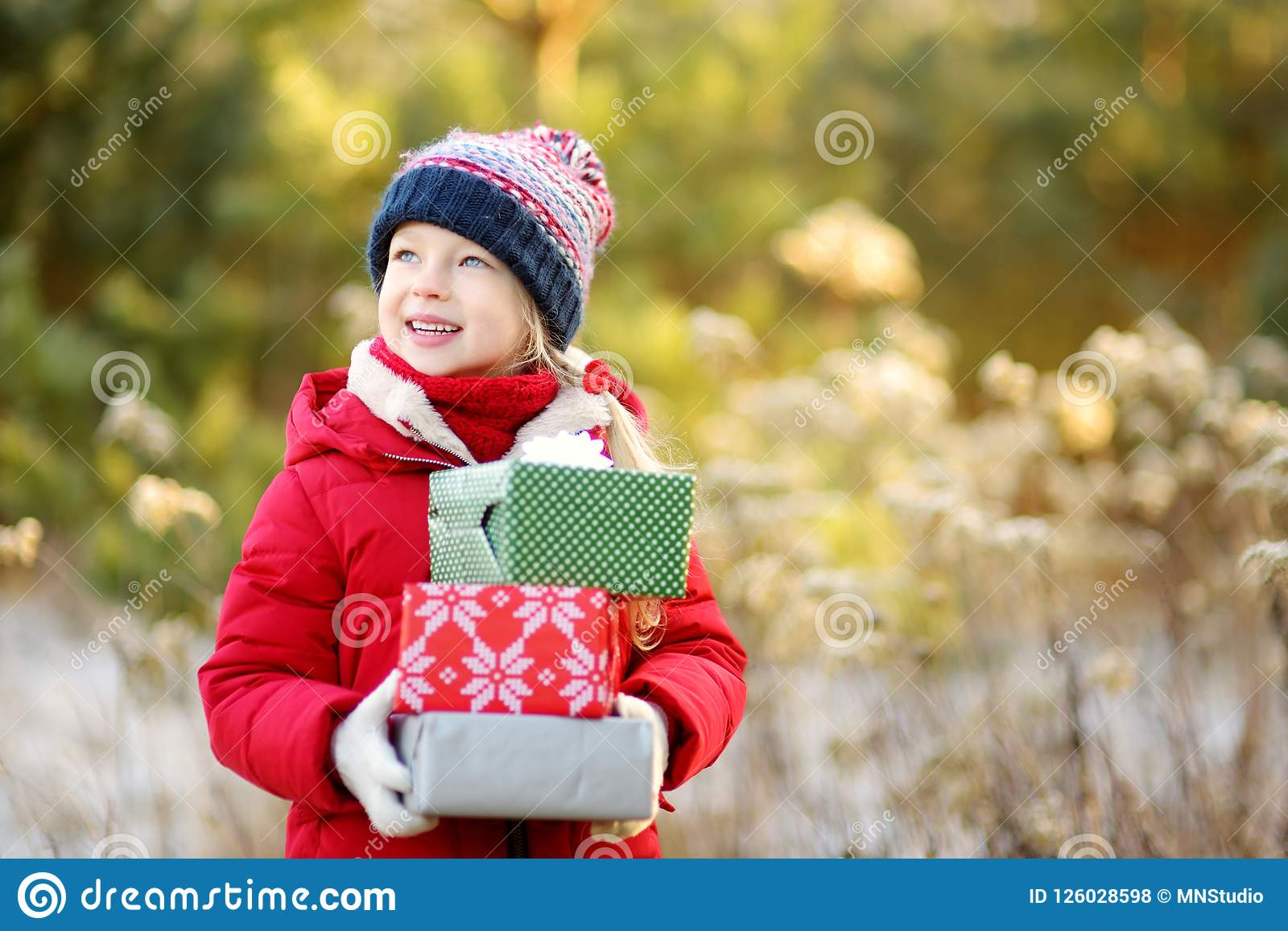 Adorable Little Girl Holding A Pile Of Christmas Gifts On Beautiful Sunny Winter Day. Stock ...