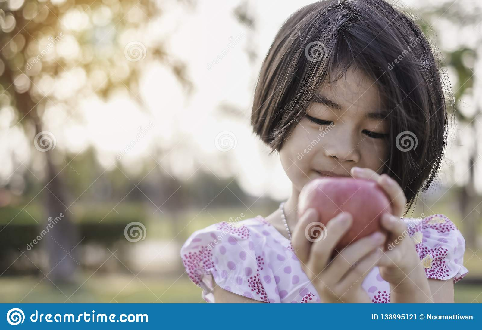 An adorable little girl holding red fresh apple
