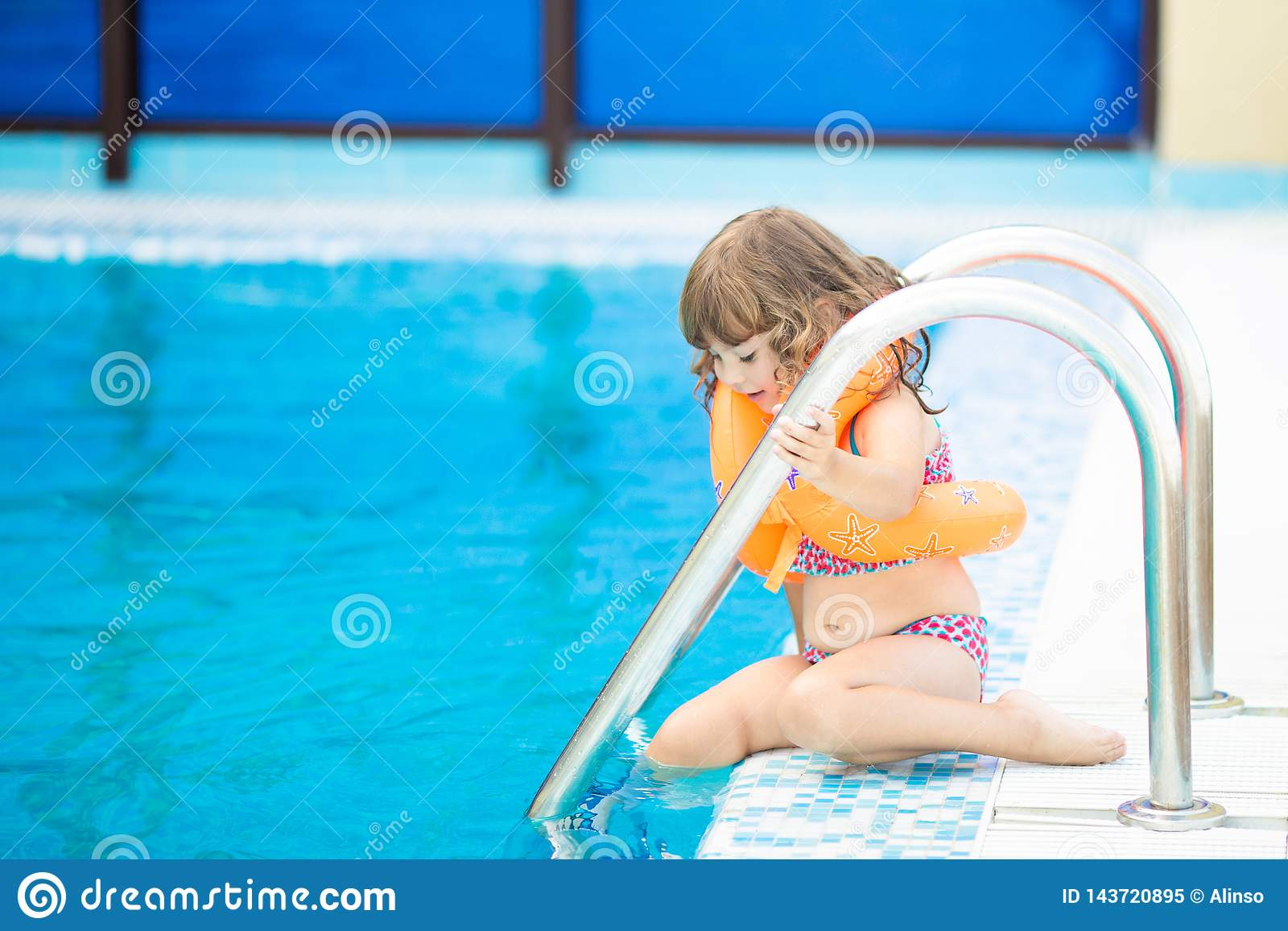 Adorable little girl with inflatable life vest having fun in the pool