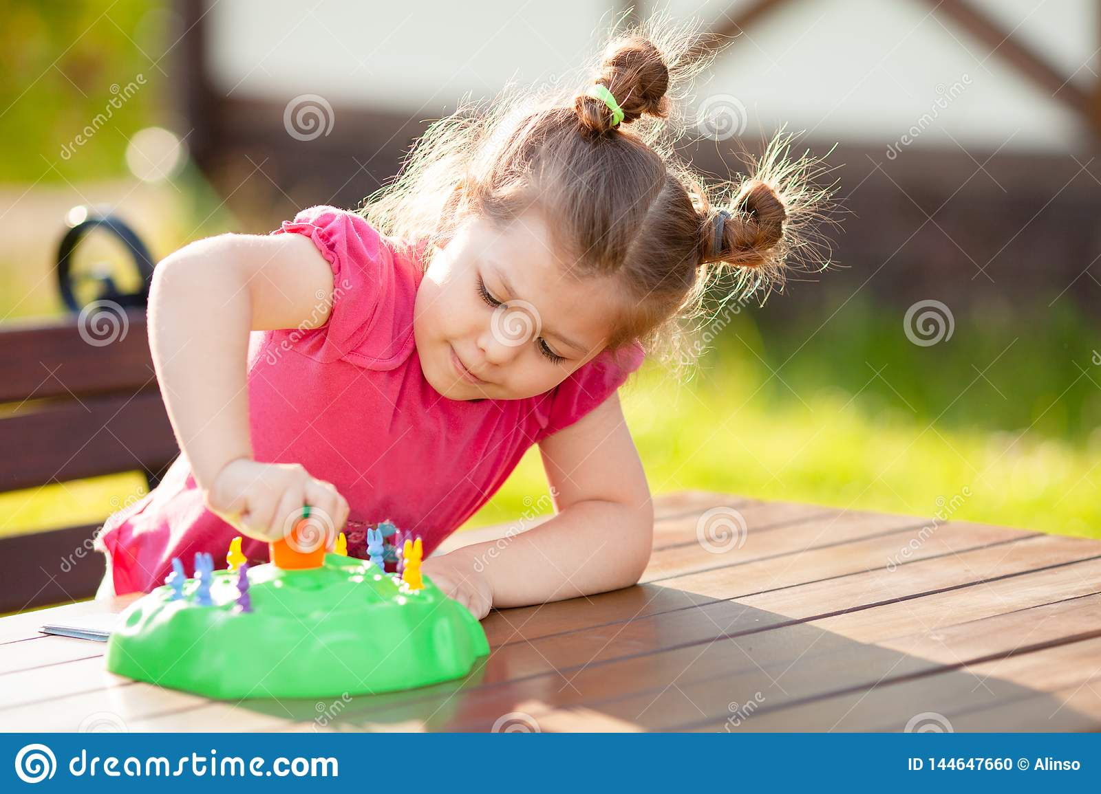 Adorable little girl playing board game outdoors