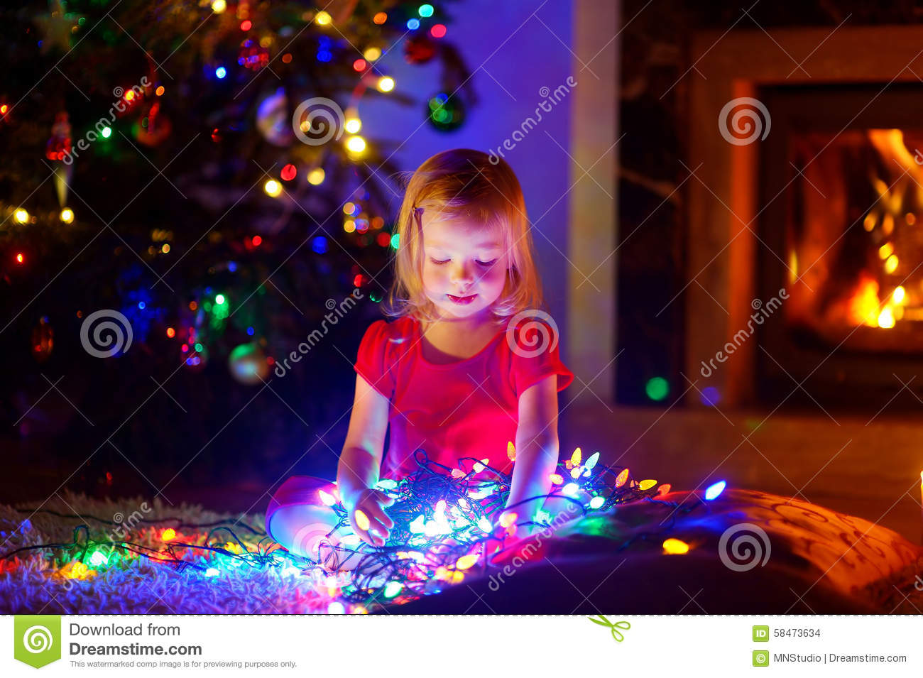 adorable little playing with christmas lights stock photo