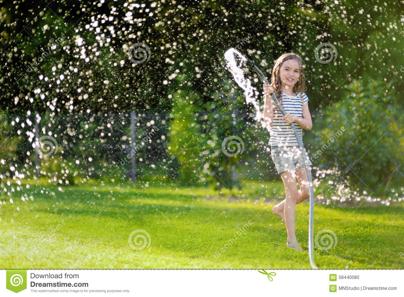 adorable little playing with a garden hose stock photo