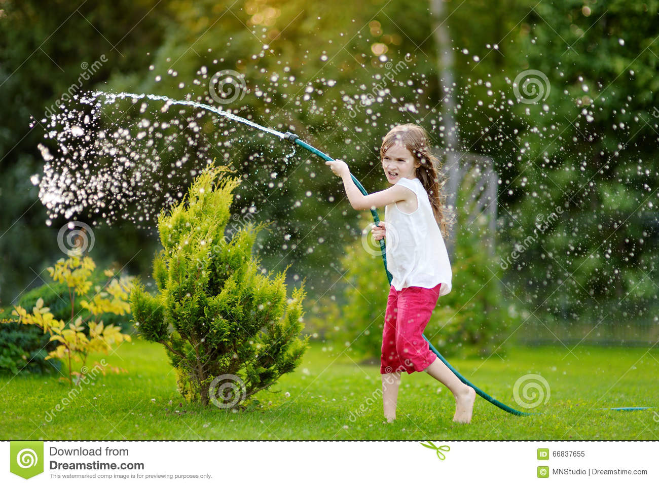 Adorable little girl playing with a garden hose on summer evening